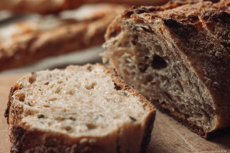 dark yeast-free buckwheat bread in a cut lies on a cutting wooden board on a wooden table next to italian grissini on a linen tablecloth in rustic style. Selective focus. Concept of making breakfast.