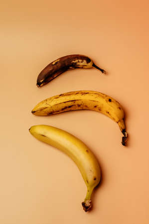 Ugly fruit modification of three bananas from ripe to more spoiled brown with spots isolated. The concept of fruit is not salable for supermarkets. Vertical orientation