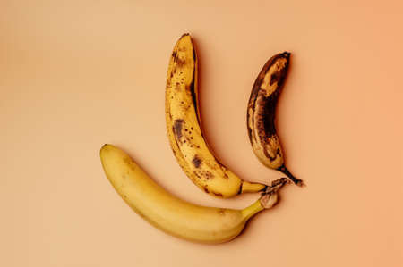 Ugly fruit modification of three bananas from ripe to more spoiled brown with spots isolated. The concept of fruit is not salable for supermarkets. Horizontal orientation