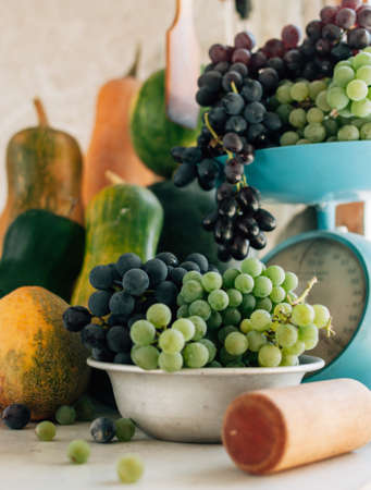 Autumn still life with pumpkins, melons, watermelon, grapes on a scale and in a metal bowl on a wooden white table. Autumn harvest concept. Happy Thanksgiving. Selective focus. Template for design.