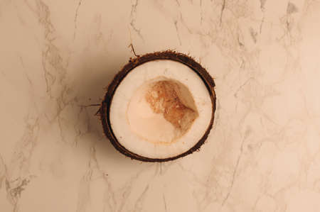 ugly organic broken rotten coconut on a marble background. a broken nut in a shell the white insides of a coconut, which began to decompose and covered with fungus and mold.