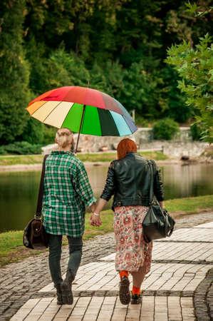Pareja de lesbianas cogidos de la mano caminando en el parque de otoño bajo la lluvia con un paraguas de arco iris. El concepto de amor libre y paseos por el parque. Comunidad LGBT