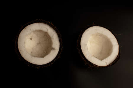 ugly organic coconut on a black background, isolate. a broken nut in a shell the white insides of a coconut, which began to decompose and covered with fungus and mold. Spoiled products. Imagens