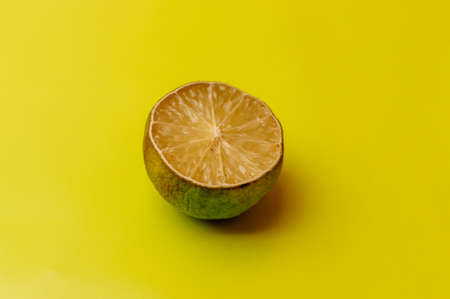 The concept of ugly fruits and citrus fruits. Half of sliced lime has dried and deteriorated on a yellow background. Mold on citrus fruits. Copy space.