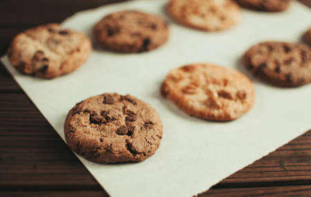 Chocolate covered cookies lay on a parchment paper in a row. Gluten-free cookies on a wooden table out of the oven. Selective focus 스톡 콘텐츠