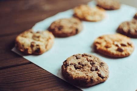 Kekse mit Schokoladenüberzug lagen hintereinander auf einem Pergamentpapier. Glutenfreie Kekse auf einem Holztisch aus dem Ofen. Selektiver Fokus Standard-Bild