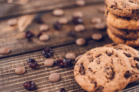 A stack of oatmeal cookies with chocolate pieces and candied fruits lies on a wooden table. Rustic table. Vintage toning. Dietary useful cookies without gluten. Copy space.