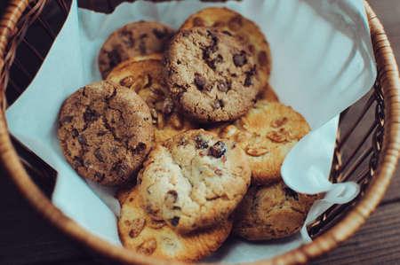 Des biscuits au chocolat se trouvent dans un panier en osier. Un panier avec des biscuits sans gluten sur une table en bois. Mise au point sélective.