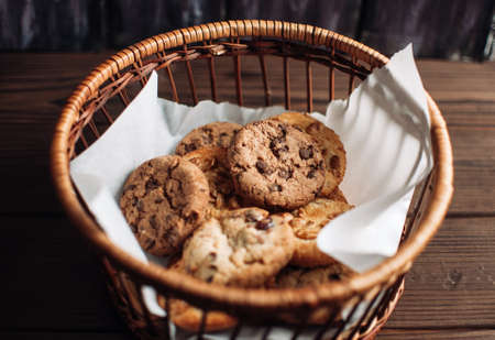 Cookies with chocolate lies in a wicker basket. A basket with gluten free cookies on a wooden table. Selective focus.