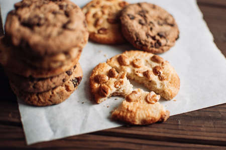 Chocolate cookies on parchment paper. Broken biscuits on a wooden table. Selective focus.