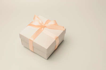 Gift box with beige ribbon on a white background, isolate. Copyspace. The concept of sales, discounts, Christmas gifts and shopping.