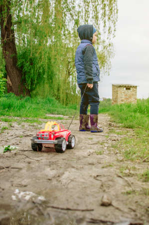 a child in a blue vest and rubber boots carries a typewriter through the mud. The boy goes outside after a summer rain. The concept of a carefree childhood. Stock Photo
