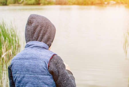 the child in the blue yolk and hood looks into the distance. The boy faces the river and looks at the water. The child walks on the street after the summer rain. The concept of a carefree childhood.