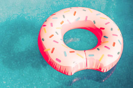 An inflatable pink donut with white icing floats in a blue pool. An inflatable circle for swimming on water in the warm season. The concept of summer spending time. Beach summer composition