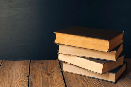 books stacked on a wooden table in a rustic style on the background a school blackboard. The concept of welcome back to school. copy space Archivio Fotografico
