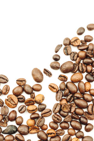 Coffee beans are scattered over the surface on a blank white background. a handful of brown coffee beans. Coffee background with copy space for lettering, text or logo. Mock up.