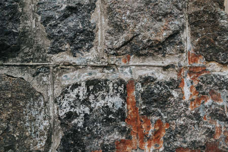 The texture of a stone medieval castle wall with natural defects. Scratches, cracks, crevices, chips, dust, roughness, abrasion. Template for design and background.Copy space