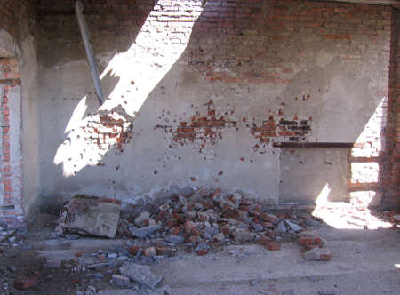 a ruined building abandoned inside with bricks gunshot marks on the walls a target for an airsoft shooting range