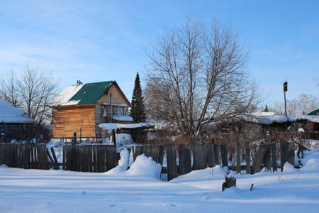 a wooden fence blocks an unfinished house in the winter in the village Redakční