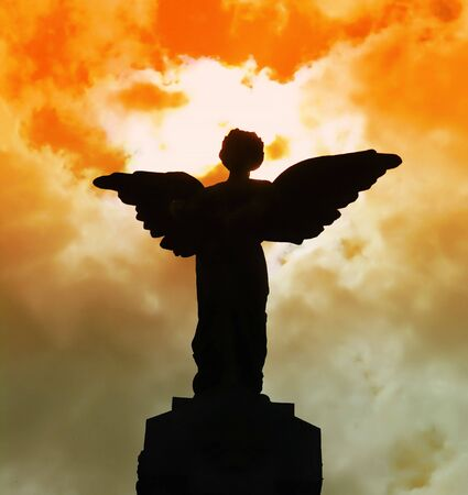 angel of death: Statue of an angel silhouetted against red clouds Stock Photo