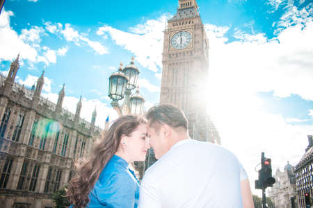 Happy couple by Big Ben, nearby River Thames, London, England, United Kingdom. Romantic young couple looking each other. Travel. Blue sky. Banque d'images