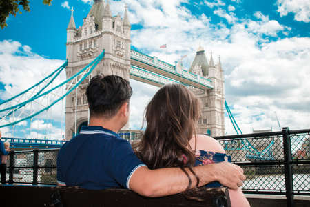 Happy couple by London Bridge, River Thames, London, England, United Kingdom. Romantic young couple enjoying view during travel. Blue sky.