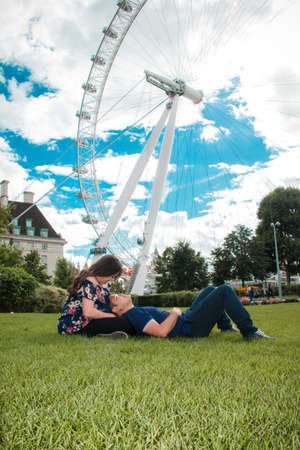 Happy couple by London Eye, River Thames, London, England, United Kingdom. Romantic young couple enjoying time at the park during travel. Blue sky. Banque d'images