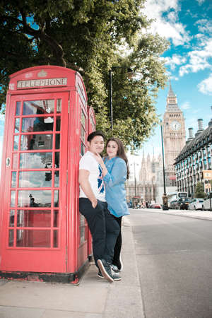 Happy couple by Big Ben, nearby River Thames, London, England, United Kingdom. Romantic young couple posing beside a telephone cabinet during travel. Blue sky.