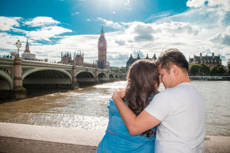 Happy couple by Big Ben, nearby River Thames, London, England, United Kingdom. Romantic young couple enjoying view during travel. Blue sky.