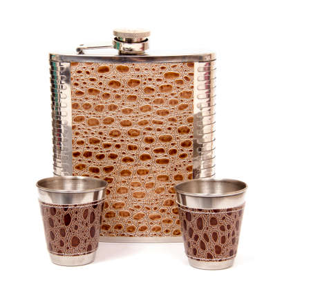 Metal flask trimmed leather and metallic sturdy shot glasses on a white background Stok Fotoğraf