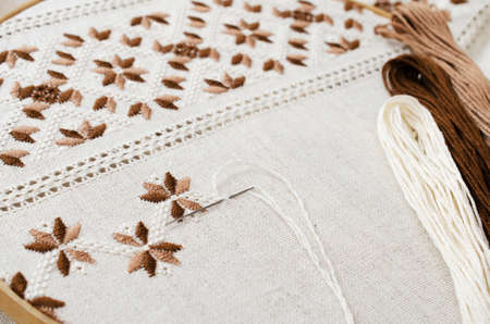 metier: The wooden hoop with the embroidery pattern of brown and beige color on canvas; on wooden table. Stock Photo