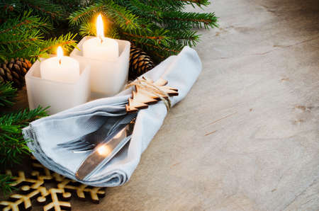 Rustic Christmas Table Setting for Christmas Eve. Winter Holydays. Cutlery on linen napkin, candles and fir branches on rustic wooden background - country style. Selective focus, space for text.