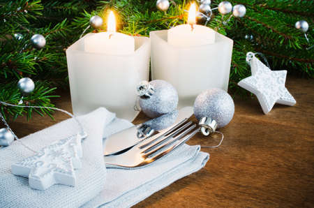 Table Place Setting for Christmas Eve. Winter Holydays. Christmas background. Cutlery on napkin, candles and fir branches on rustic wooden background. Selective focus.