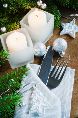 holydays: Table Place Setting for Christmas Eve. Winter Holydays. Christmas background. Cutlery on napkin, candles and fir branches on rustic wooden background. Selective focus.
