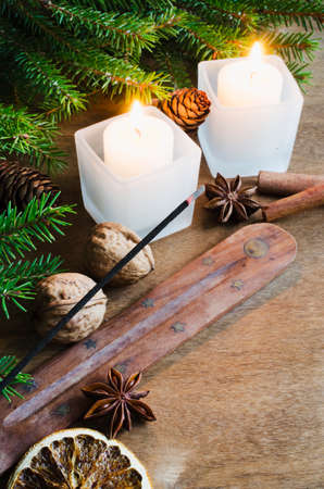 romantic places: Christmas Background. Winter Holidays. Festive Evening. Incense, Candles and Fir Branches on Rustic Wooden Background. Selective Focus.