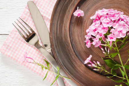 Spring table settings with fresh flower, napkin and silverware. Holidays background. Selective Focus. Stock Photo