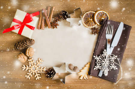 card making: Culinary Background. Empty Paper for Recipe of Christmas Baking. Set Cutlery and Present Box on napkin. Top view. Copy space. Selective focus. Snow Effect. Toned Image. Stock Photo