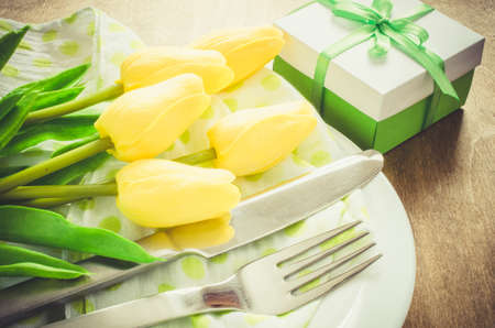 Festive Table Setting in White, Green and Yellow With Tulip. Concept Spring, Easter or Mothers Day. Selective Focus. Toned Image. Stock Photo