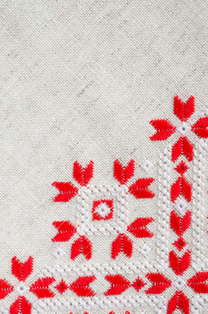 Embroidery design by red and white cotton threads on flax. Geometric ornament. Christmas background with embroidery.
