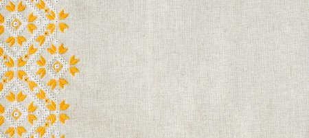 Borduurontwerp door geel en wit katoenen draden op vlas. Geometrische versiering. Achtergrond met borduurwerk voor banner.