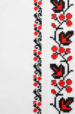 Ukrainian folk patterns embroidered with a cross on a white canvas. Slavic Embroidery for background.