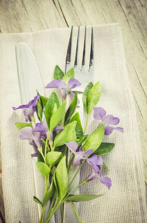 Festive Table setting with delicate purple flowers. Holiday Table Set for Mothers Day or Birthday. Selective Focus.
