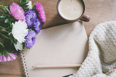 Flat lay of blank brown notebook with autumn flowers and cup of coffee on wooden table. Copy space. 写真素材