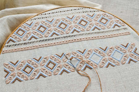 Embroidered fragment on flax by brown and beige cotton threads. Macro embroidery texture flat stitch. Ukrainian ethnic ornament.