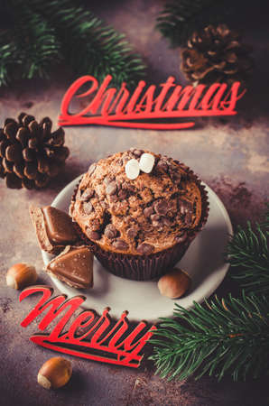 Chocolate muffin and branches fir. Christmas time. Selective Focus. Copy space. Vintage stile. Toned image Archivio Fotografico
