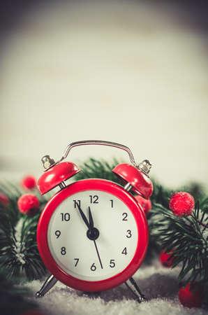 雪で覆われたモミの木の枝との真夜中にクリスマスイブと新年の時計。ヴィンテージトーンのイメージ。