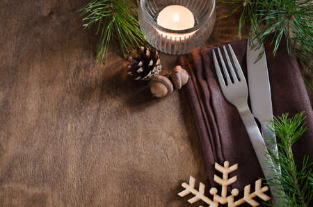stock photo vintage or rustic christmas table setting with candle and wooden decorations cutlery on linen napkin on rustic wooden background country