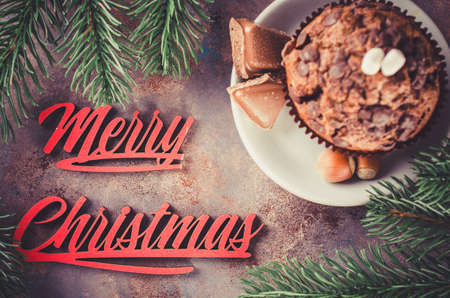 Chocolate muffin and branches fir. Merry christmas inscription. Selective Focus. Copy space. Vintage stile. Toned image Archivio Fotografico