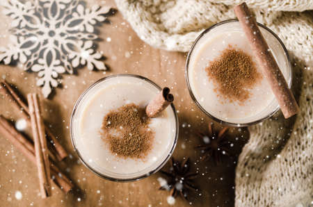 Traditional Homemade Winter Eggnog Cocktail with Whipped Cream and Cinnamon for Christmas Eve and Winter Holidays. Selective Focus. Snow effect. Stock Photo