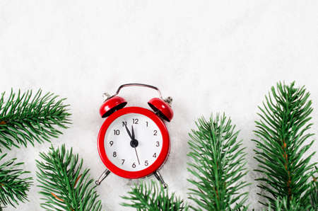 Christmas Eve and New Years clock at midnight with fir tree branches on snow. Stock Photo